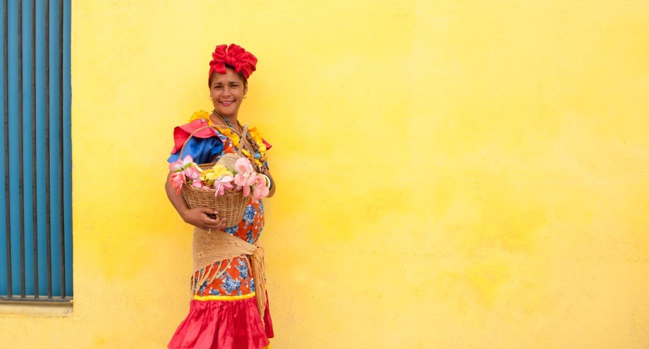 Cuba-woman_yellow-wall-2-1300x700