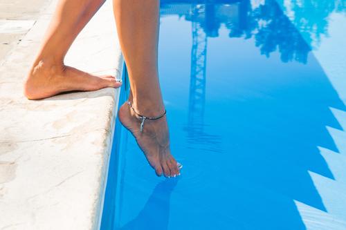 Closeup portrait of female legs near swim pool